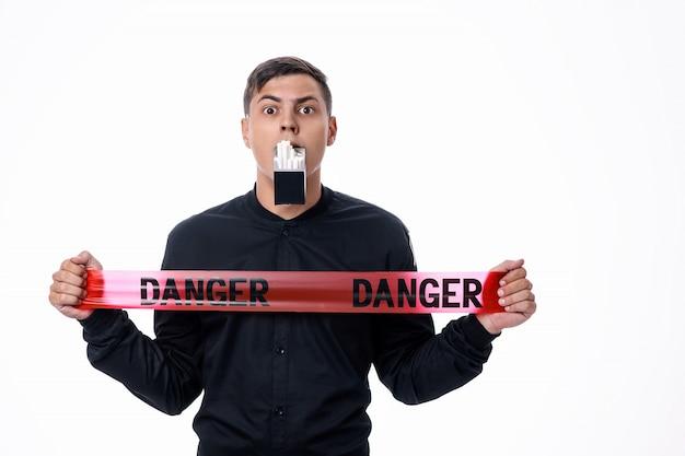 Испуганный мужчина в черной рубашке держит во рту пачку сигарет и красную ленточку в руках со словами «опасность». здоровый образ жизни. плохие привычки.