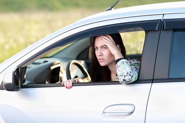 자동차의 창 밖을 바라 보는 겁 먹은 화난 여자