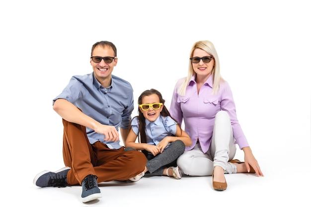 흰색 배경에 격리된 캐주얼 복장을 하고 3d 안경을 쓰고 영화를 보는 겁에 질린 매력적인 가족
