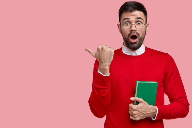 Испуганный бородатый мужчина указывает большим пальцем на пустое место для копий, открывает рот от недоумения, держит зеленый блокнот