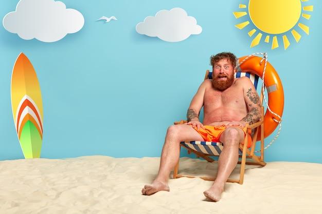 おびえたひげを生やした赤毛の男がビーチで日焼けする