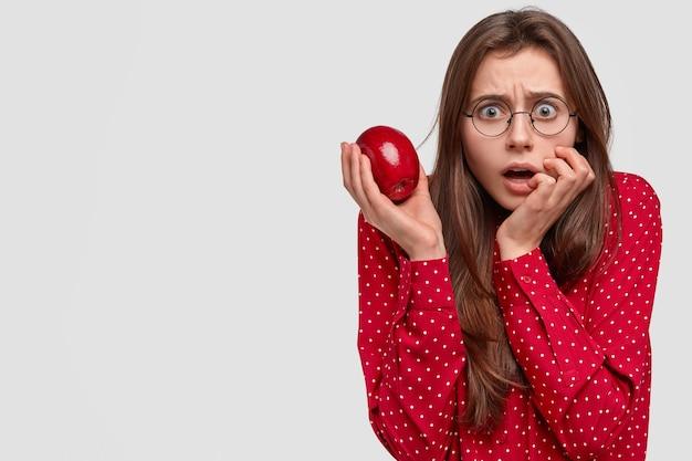 La bella signora emotiva spaventata guarda direttamente con un'espressione spaventosa, tiene in mano la mela rossa fresca