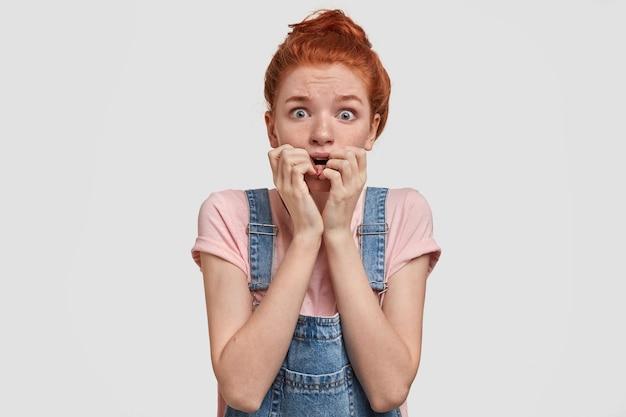 おびえた美しいそばかすのある女性が神経質に指の爪を噛む