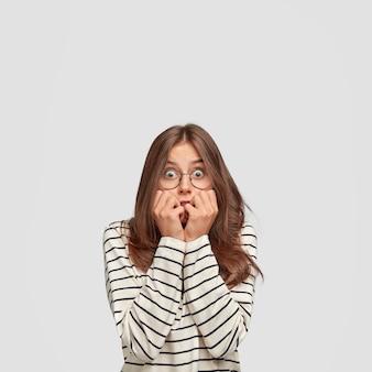 おびえた美しい若い女性は指の爪を噛み、心配そうに見え、ファッショナブルな服を着て、魅力的な外観を持ち、白い壁に立っています。人、感情の概念。