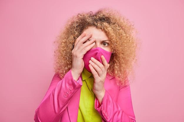 おびえた巻き毛のヨーロッパ人女性は、何か恐ろしいものを恐れて顔を隠している フォーマルな服装でピンクの壁に対してポーズをとる コロナウイルスの影響を受けるのを恐れて、保護フェイスマスクを着用している