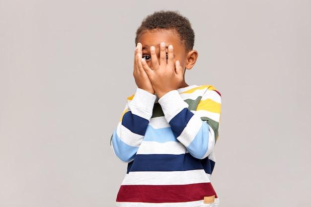 指の間の穴から何か怖いものを見るのを恐れているかのように、両手で顔を覆っているおびえた黒い肌の小さな男の子。恥ずかしがり屋のアフリカの子供が隠れたり、かくれんぼをしたりする