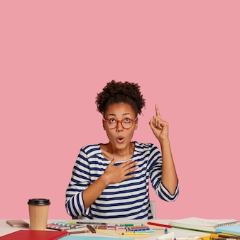 Frightened emotional dark skinned female designer raises index finger, keeps hand on breast, points upwards, notices unbelievable item, uses notebook, caryons for making sketch sits in coworking space