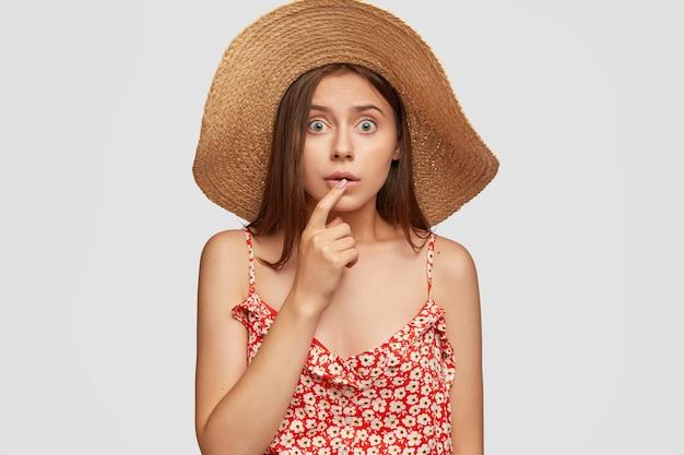 Испуганная эмоциональная кавказская женщина смотрит с вытаращенными глазами, держит указательный палец на губах, смотрит в недоумении