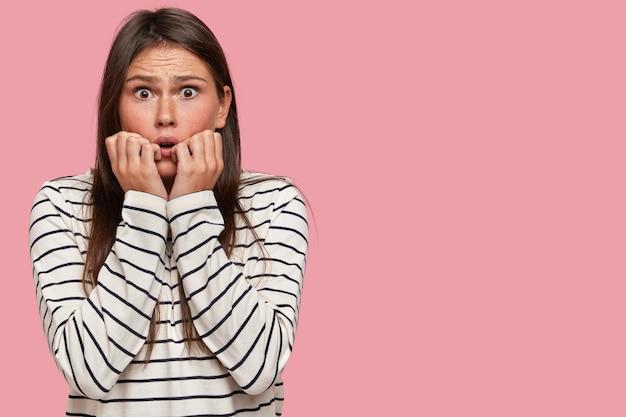 Напуганная эмоциональная женщина держит обе руки у рта, смотрит вытаращенными глазами, кусает ногти пальцами, нервничает