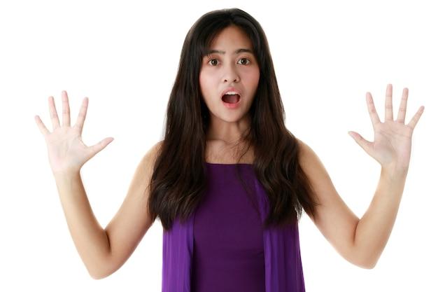 スタジオで白い背景の上のカメラを見て口を開けたおびえた民族の女性。