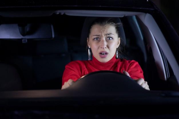 おびえた女性ドライバーが道路で自動車事故を起こしている