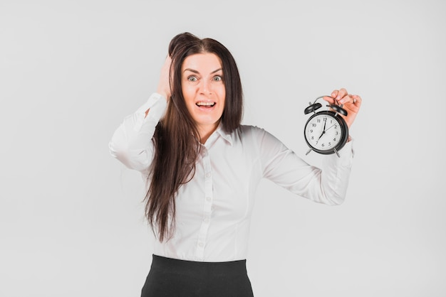 Frightened female holding hair and alarm clock