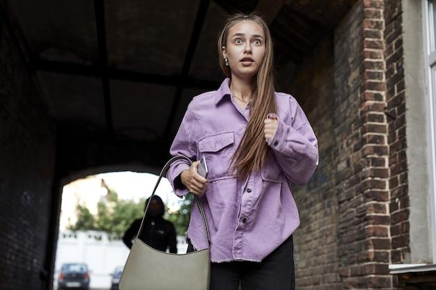 おびえた女性は昼間一人で通りを走っています。アクション。彼女に続くレイプ犯の殺人者を恐れている女性。泥棒から逃げる怖い白人女性。犯罪、暴力の概念