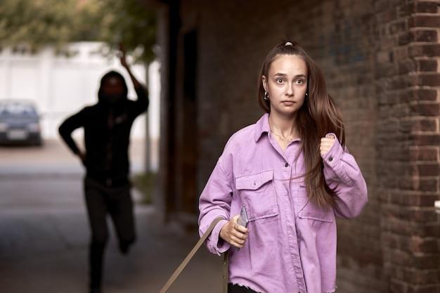 おびえた女性は昼間一人で通りを走っています。アクション。レイプ犯を恐れる女