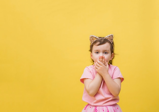 The frightened girl covers her mouth with her hands on a yellow space. a little girl with a cat-ear headband is surprised. cute girl in a pink t-shirt with a pocket.