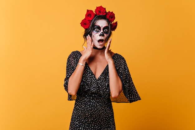 Frightened girl in halloween mask opened her mouth in surprise. portrait of woman in polka dot dress on isolated wall.