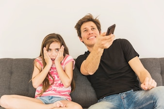Frightened girl sitting with her father holding remote control