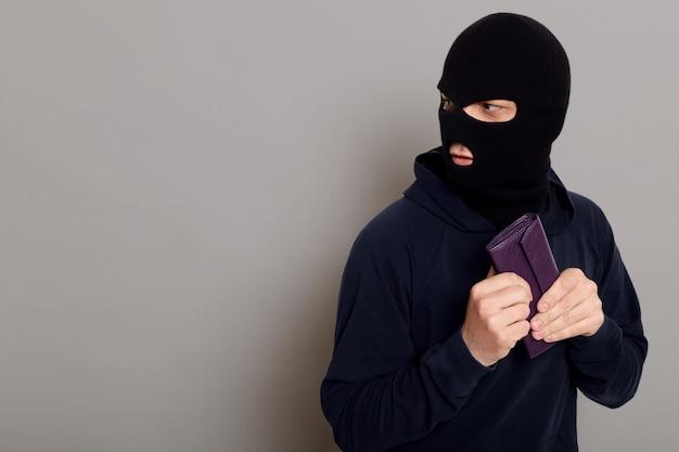 Испуганный вор парень одет в черную толстовку с капюшоном