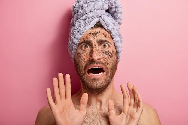 Spaventato bel giovane uomo caucasico con caffè macchia sul viso, fa il gesto di arresto, afraids di trattamenti termali, indossa asciugamano