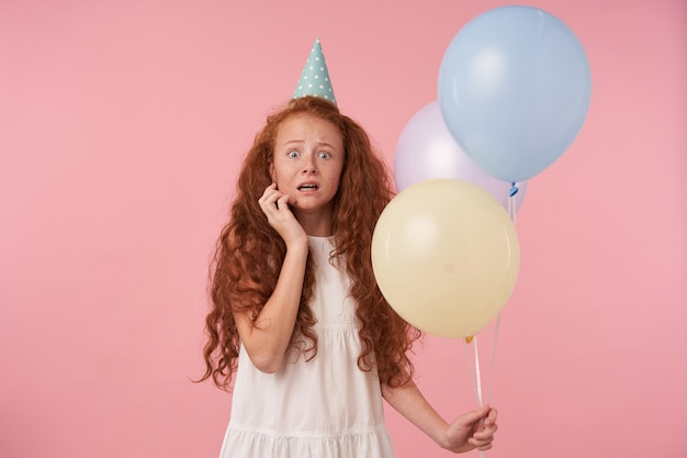 Frightened hredhead curly girl with long hair wearing white elegant dress, keeping hand on her face and looking scarely to camera, isolated over pink background with air balloons in hand