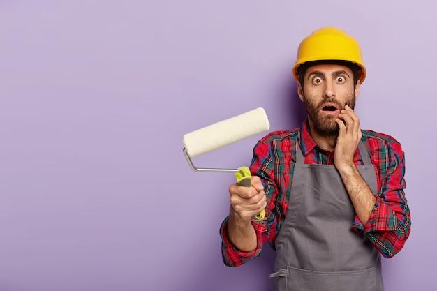 Il lavoratore industriale spaventato indossa elmetto protettivo e grembiule gialli