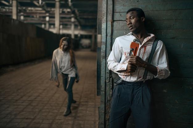Испуганный мужчина прячется от зомби-женщины на заброшенной фабрике. ужас в городе, жуткие ползания, апокалипсис судного дня, кровавые злые монстры