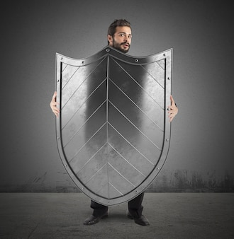 Испуганный человек прячется за большим щитом
