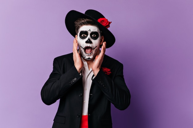 Frightened man in wide-brimmed hat looking in horror at camera. portrait of guy with halloween makeup posing on purple background.