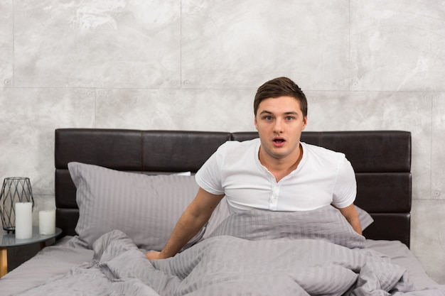 Frightened man woke up from a nightmare sitting in stylish bed with grey colors and near bedside table with candles in a bedroom in loft style