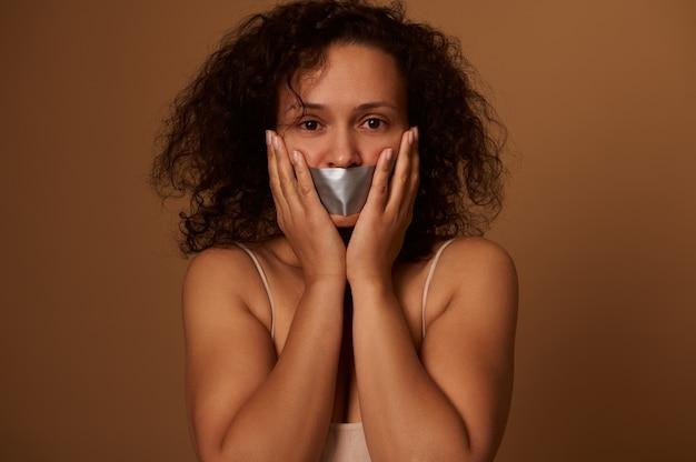 입을 막고 겁에 질린 혼혈 여성은 카메라를 필사적으로 쳐다보며 복사 공간이 있는 어두운 색 배경에 고립되어 뺨에 손을 얹고 있습니다. 개념, 여성에 대한 폭력을 중지