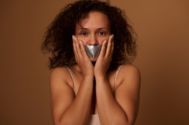 Frightened mixed race woman with sealed mouth looks desperately at camera, holding her hands on her cheeks, isolated on dark colored background with copy space. concept, stop violence against women