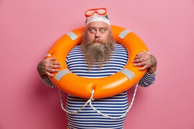 Il vacanziere in sovrappeso spaventato soffre di affondamento, utilizza attrezzature di sicurezza, indossa occhiali da snorkeling, nuota con il salvagente, guarda direttamente con espressione scioccata. assicurazione di viaggio