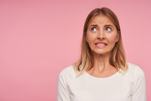 Frightened pretty blue-eyed woman with blonde hair looking scaredly upwards and showing her white teeth, wearing casual clothes while standing over pink background