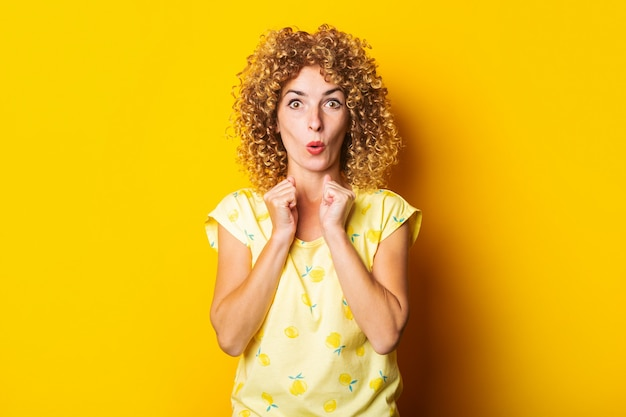 黄色の背景に握りこぶしを握っておびえた驚いた縮れ毛の若い女性