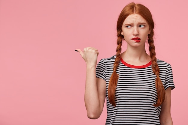 Испуганная неуверенная в себе испуганная рыжеволосая девушка с двумя косами в полосатой футболке, указывающая большим пальцем влево на копировальном пространстве, смотрит туда с недоверием, прикусывает губу, изолирована на розовой стене