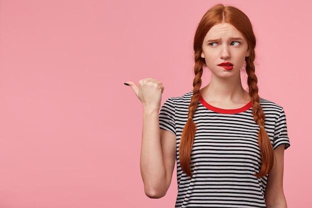 Ragazza dai capelli rossi spaventata non sicura di sé con due trecce in maglietta spogliata che punta con il pollice verso il lato sinistro sullo spazio della copia e guarda lì con diffidenza, si morde il labbro, isolato sul muro rosa