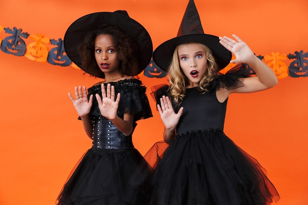 Frightened witch girls in black halloween costumes looking at camera and showing stop gesture isolated over orange pumpkin wall