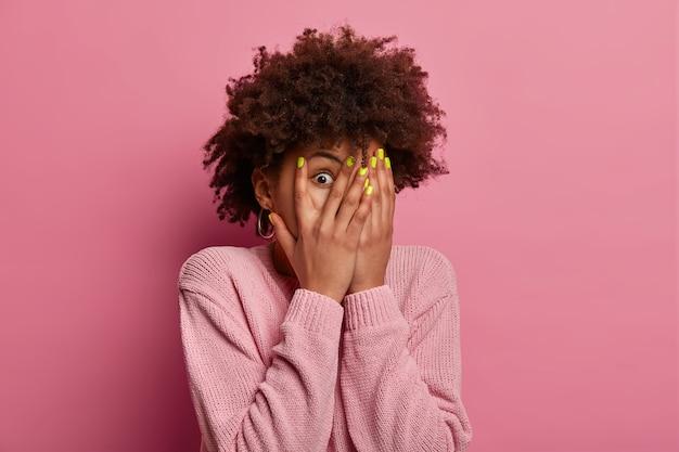 おびえた女性は手のひらで顔を覆い、指で覗き、恐ろしくて予想外の何かを見て、あらゆる困難から身を隠し、何が起こっているのか興味をそそられ、壁とワントーンでジャンパーを身に着けています