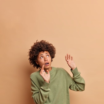Испуганная женщина держит руки поднятыми, пытается остановить что-то, упавшее вверх, сосредоточенно вверх, боясь, носит повседневный джемпер, позирует на фоне бежевой стены.