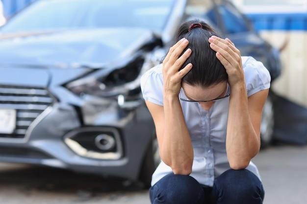 겁 먹은 여성은 자동차 사고 개념 후 난파된 자동차 운전자의 스트레스 앞에 앉는다