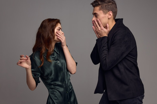 A frightened woman and a surprised man look at each other against a gray background. high quality photo