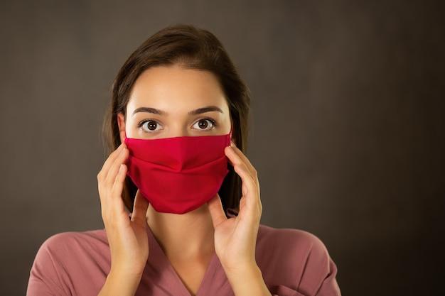 ピンクのマスクに指で触れるおびえた女性