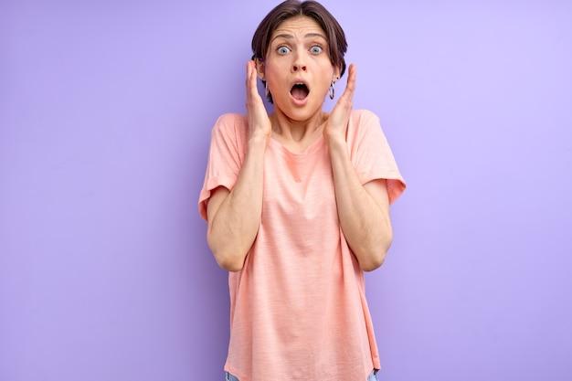 恐怖で叫び、紫色の背景で隔離のカメラを見て基本的なtシャツの短い茶色の髪のおびえた女性