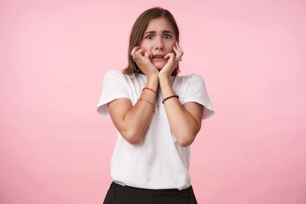 Испуганная молодая кареглазая брюнетка со стрижкой боб держит лицо поднятыми руками, испуганно глядя вперед, стоя над розовой стеной