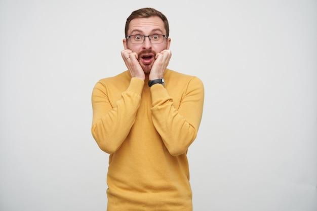 Испуганный молодой бородатый брюнет в очках смотрит с широко открытыми глазами и открытым ртом, держа руки на лице стоя