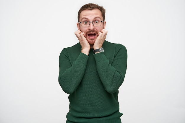 Испуганный молодой брюнет с бородой в очках и зеленом свитере стоя, испуганно округляя глаза с открытым ртом