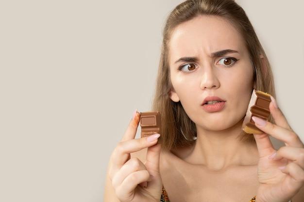 チョコレートのかけらを探しているおびえた若いブルネットの女性