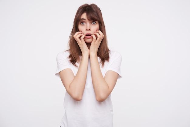 カジュアルな髪型でおびえた若いブルネットの女性は、手を上げて顔を保ち、怖く見ながら青い目を丸め、白い壁に隔離