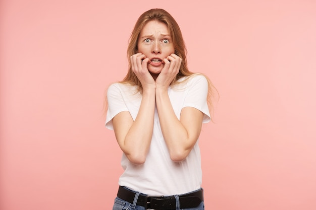 Frightened young green-eyed redhead woman with natural makeup holding her face with raised hands while looking scaredly at camera, standing over pink background
