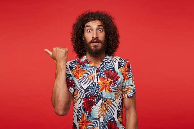 Frightened young pretty bearded man with curly brown hair rounding eyes amazedly and pointing aside with raised hand, wearing multi-colored flowered shirt while posing against red background